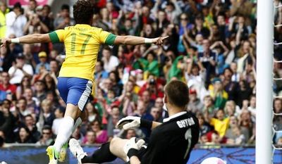 Brazil's Alexandre Pato, top, celebrates after scoring past Belarus' goalkeeper Aleksandr Gutor during their group C men's soccer match at the London 2012 Summer Olympics, Sunday, July 29, 2012, at Old Trafford Stadium in Manchester, England. (AP Photo/Jon Super)