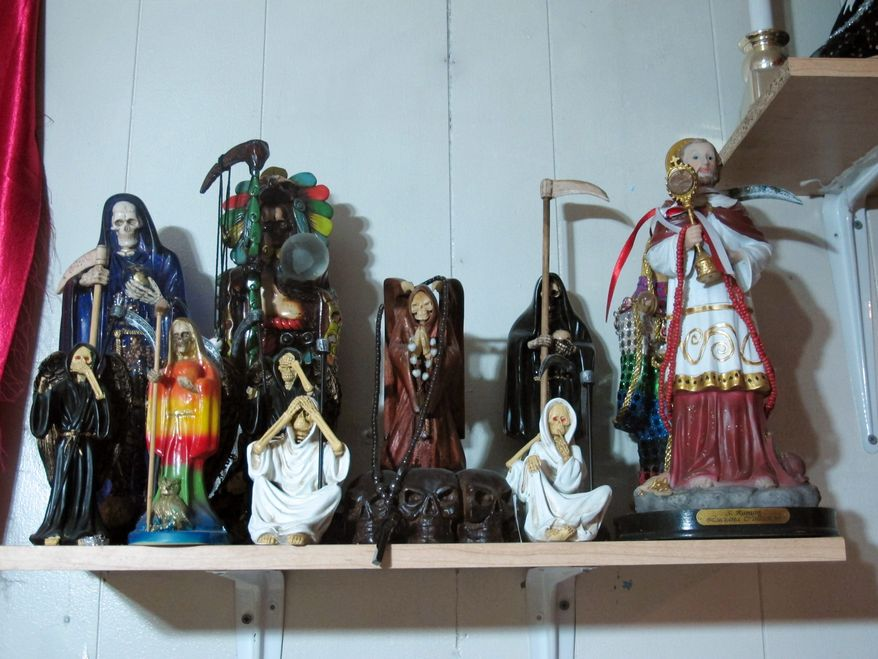 ** FILE ** In this Feb. 12, 2013, photo, statues of La Sante Muerte from an altar run by Arely Vazquez Gonzalez, a Mexican immigrant and transgender woman, is shown inside a Queens, NY apartment. La Santa Muerte, an underworld saint most recently associated with the violent drug trade in Mexico, now is spreading throughout the U.S. among a new group of followers ranging from immigrant small business owners to artists and gay activists. (AP Photo/Russell Contreras)