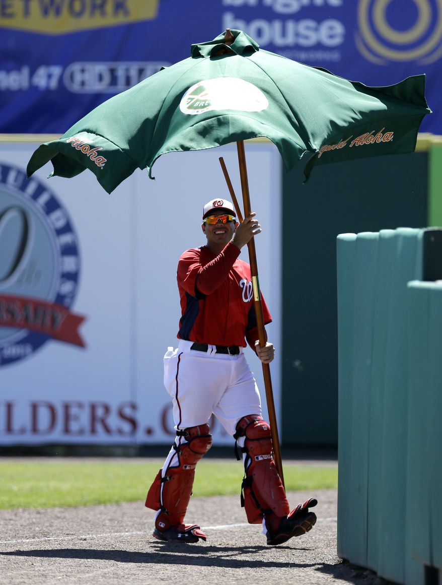 Washington Nationals bullpen catcher Octavio Martinez removes an umbrella which blew onto the field during the second inning of an exhibition spring training baseball game against the Houston Astros Tuesday, March 5, 2013, in Viera, Fla. (AP Photo/David J. Phillip)