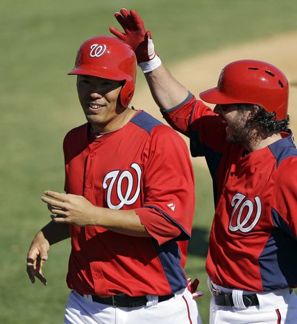 Washington Nationals' Kurt Suzuki, left, is congratulated by teammate Will Rhymes, right, after both scored on a hit by Danny Espinosa during the sixth inning of an exhibition spring training baseball game against the Houston Astros Tuesday, March 5, 2013, in Viera, Fla. (AP Photo/David J. Phillip)