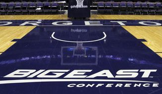 **FILE** In this Dec. 15, 2012, file photo, a Big East Conference logo is displayed on the court after Georgetown played Western Carolina in an NCAA college basketball game at the Verizon Center in Washington. Big East football schools will get almost all of a $110 million pot in a deal that will allow seven departing basketball schools to keep the name Big East and start playing in their own conference next season, a person familiar with the negotiations says. The basketball schools, which include Georgetown, St. John's, Villanova, Seton Hall, Providence, Marquette and DePaul, will receive $10 million, keep the conference name and the right to play their conference tournament at Madison Square Garden. (AP Photo/Jacquelyn Martin, File)