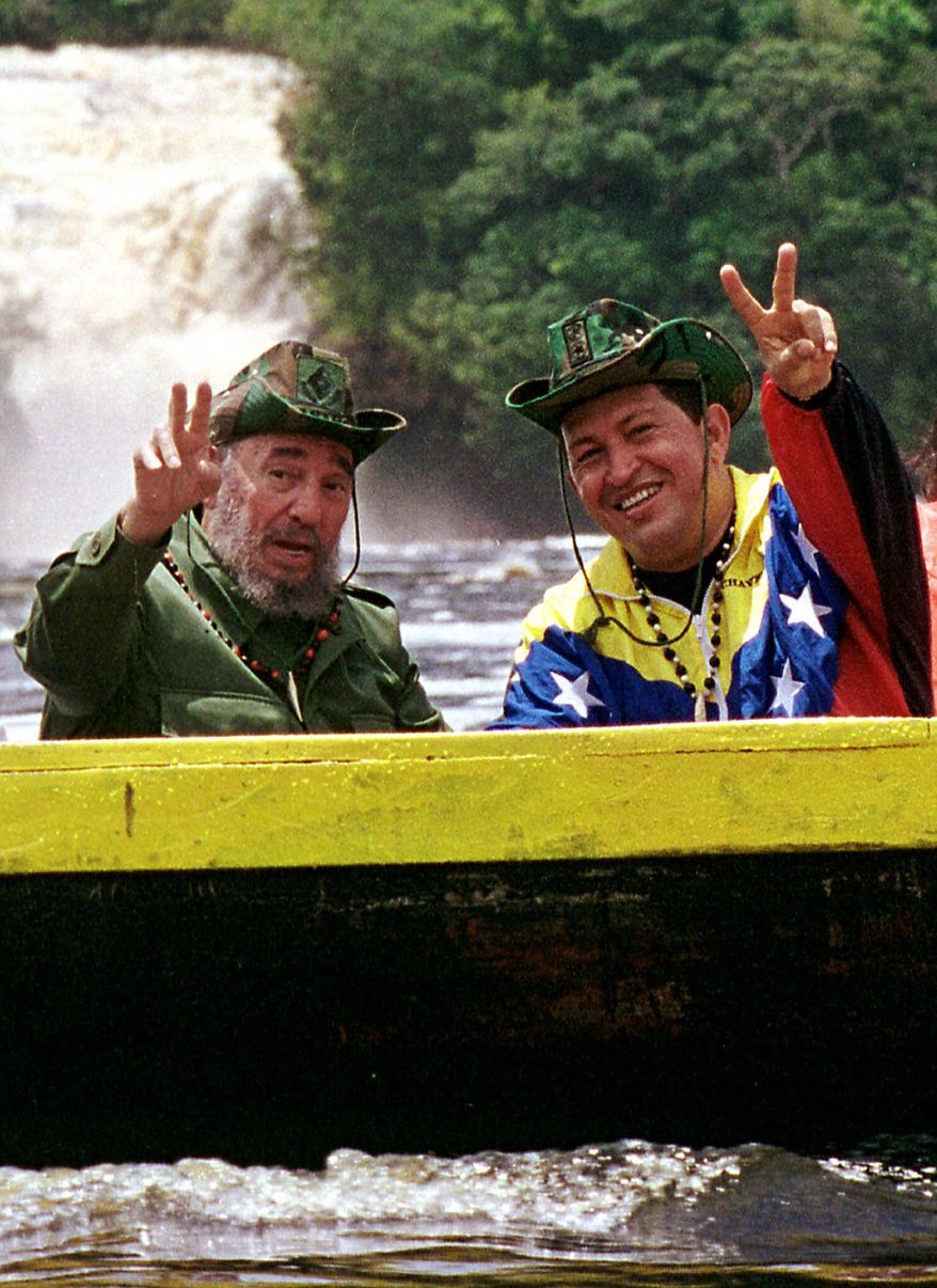 FILE - In this Aug. 12, 2001 file photo released by Miraflores Press Office, Cuba's President Fidel Castro, left, and Venezuela's President Hugo Chavez wave to a crowd while touring Canaima National Park in eastern Venezuela in a canoe. Venezuela's Vice President Nicolas Maduro announced on Tuesday, March 5, 2013 that Chavez has died at age 58 after a nearly two-year bout with cancer. (AP Photo/HO, Miraflores Presidential Palace, Egilda Gomez, File)