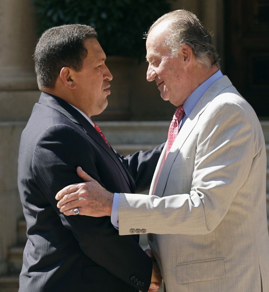 FILE - In this  July 25, 2008 file photo, Spain's King Juan Carlos, right, shakes hands with Venezuela's President Hugo Chavez at the Marivent Palace in Palma de Mallorca, Spain. Venezuela's Vice President Nicolas Maduro announced on Tuesday, March 5, 2013 that Chavez has died at age 58 after a nearly two-year bout with cancer. (AP Photo/Manu Mielniezuk, File)