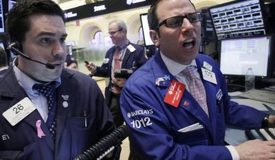 Michael Pistillo, Jr. (right), with Barclays, calls out the price of Tiffany & Co. stock to Joseph Lawlor at the New York Stock Exchange on March 5, 2013. (Associated Press)