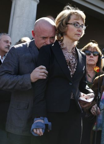 Former Rep. Gabrielle Giffords listens to a speaker as her husband Mark Kelly hugs her March 6, 2013, in Tucson, Ariz., during a return to the site of a shooting that left her critically wounded to urge key senators to support expanded background checks for gun purchases. (Associated Press)