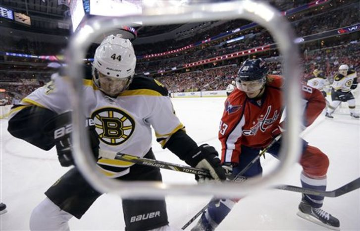 Boston Bruins defenseman Dennis Seidenberg (44), from Germany, and Washington Capitals center Jay Beagle (83) work the puck in the first period of an NHL hockey game Tuesday, March 5, 2013 in Washington. The Capitals won 4-3 in overtime. (AP Photo/Alex Brandon)