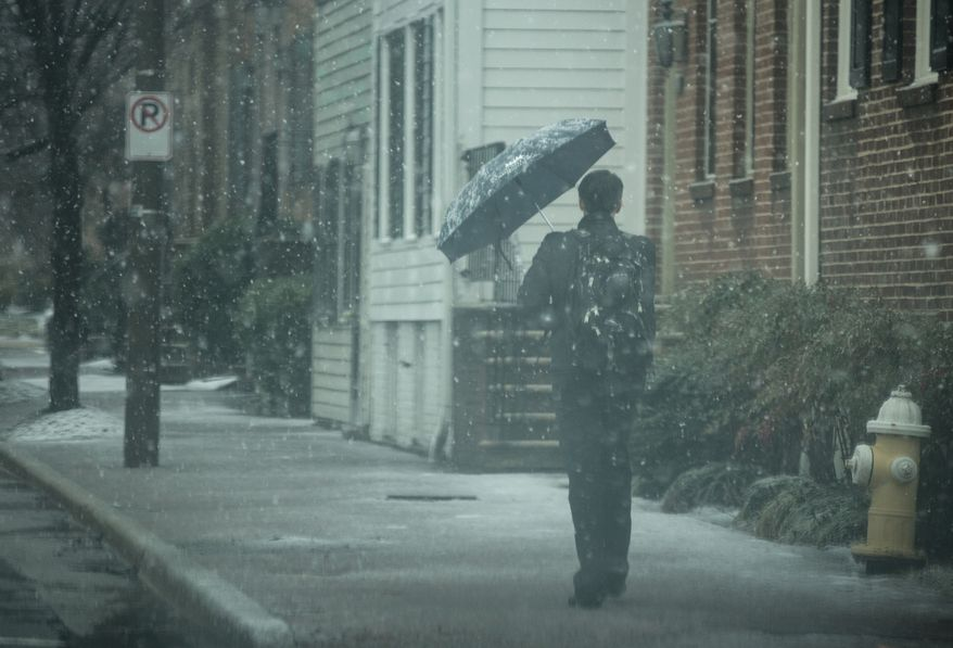 An Old Town resident uses his umbrella to shield his face from the snow in Alexandria, Va., Wednesday, March 6, 2013. (Andrew S. Geraci/The Washington Times)