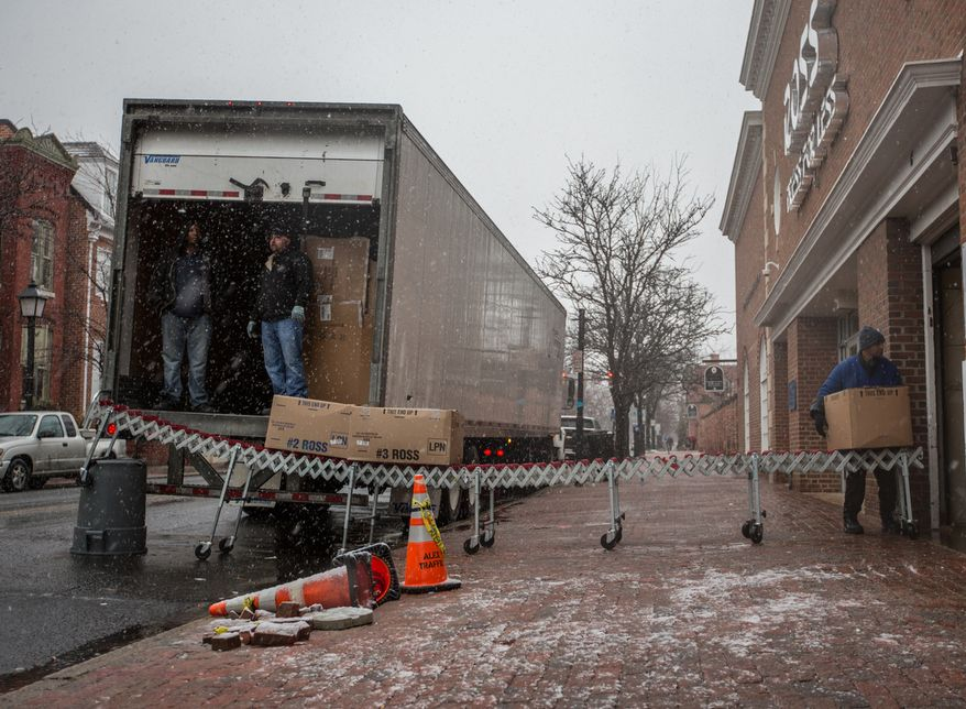 Truck workers for Ross department store, unload boxes of merchandise in the snow in Alexandria, Va., Wednesday, March 6, 2013. (Andrew S. Geraci/The Washington Times)