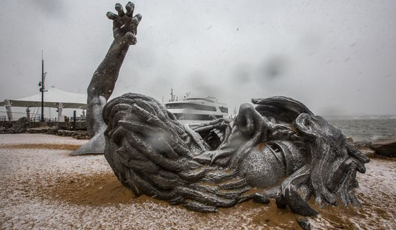 Light snow blankets 'The Awakening' sculpture, located at National Harbor in Washington, D.C., Wednesday, March 6, 2013. (Andrew S. Geraci/The Washington Times)