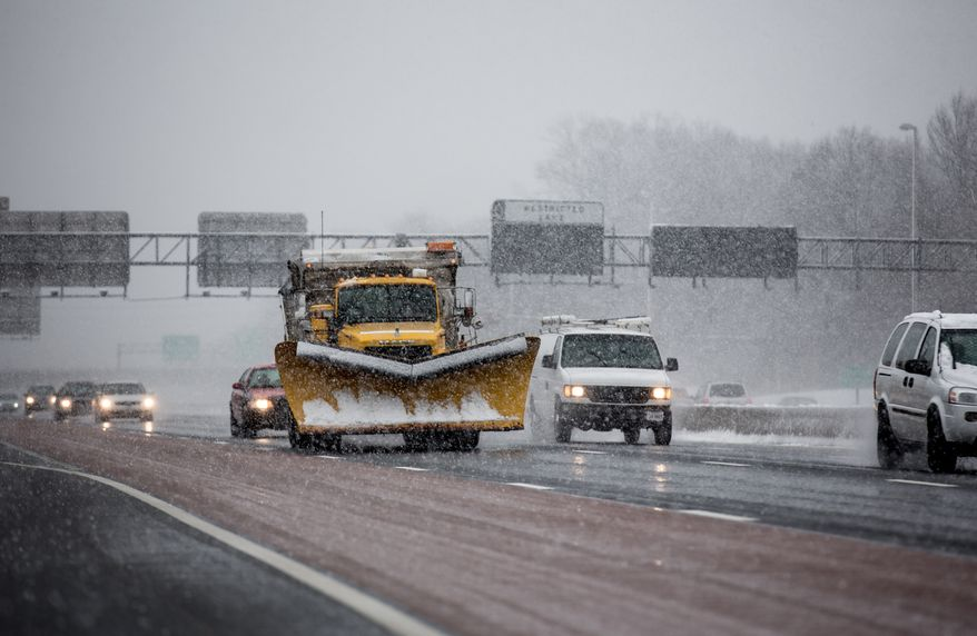 A snowplow dispenses salt as it rolls down I-66, near Route 50 in Fairfax, Va., on March 6, 2013. (Andrew S. Geraci/The Washington Times)