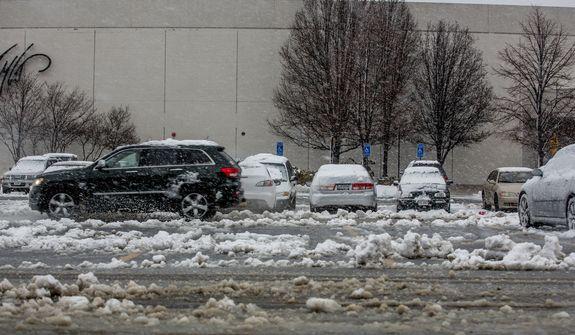 An SUV drives through the slushy parking lot of Fair Oaks Mall in Fairfax, Va., on March 6, 2013. (Andrew S. Geraci/The Washington Times)