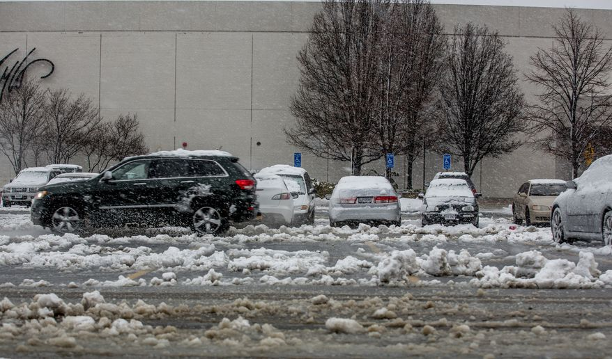 An SUV drives through the slushy parking lot of Fair Oaks Mall in Fairfax, Va., on March 6, 2013. (Andrew S. Geraci/The Washington Times)