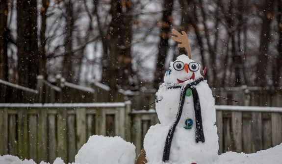 A freshly made snowman is adorned with a scarf and accessories in a neighborhood in Fairfax, Va., on March 6, 2013. (Andrew S. Geraci/The Washington Times)