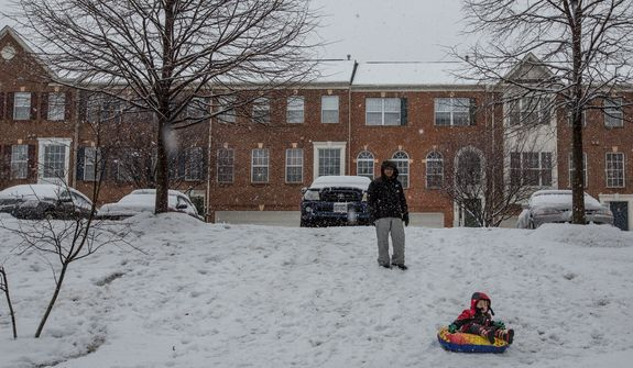 Haeyong Lee and his son, Matthew, 2, prepare to sled down a hill while it snows in a neighborhood in Fairfax, Va., on March 6, 2013. (Andrew S. Geraci/The Washington Times)