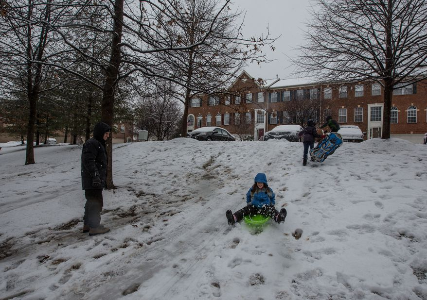 Children sled down a small hill while their parents watch in a neighborhood in Fairfax, Va., on March 6, 2013. (Andrew S. Geraci/The Washington Times)