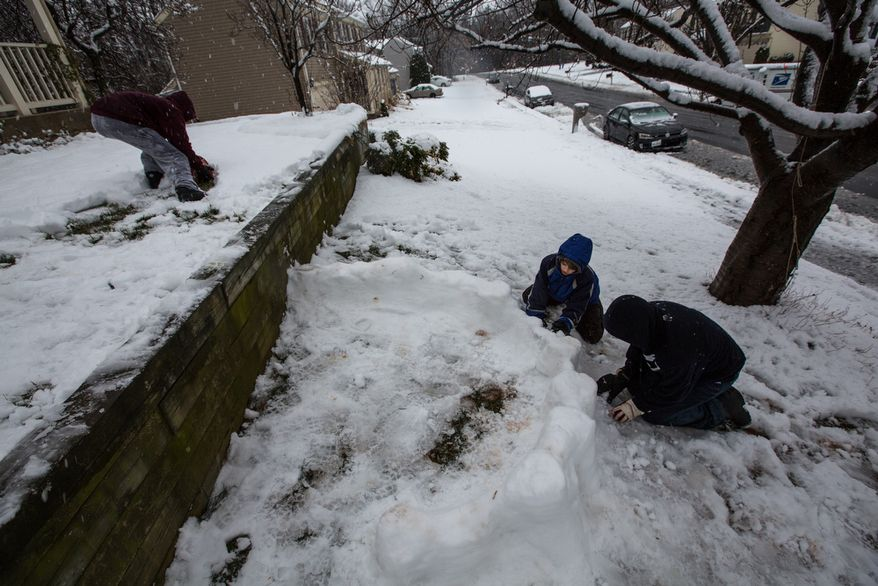 Mason Moy (left), 14, Calvin Crist (center), 13, and Sam Gustason, 13, build a snow fort in a front yard during a snow day in Fairfax, Va., on March 6, 2013. (Andrew S. Geraci/The Washington Times)