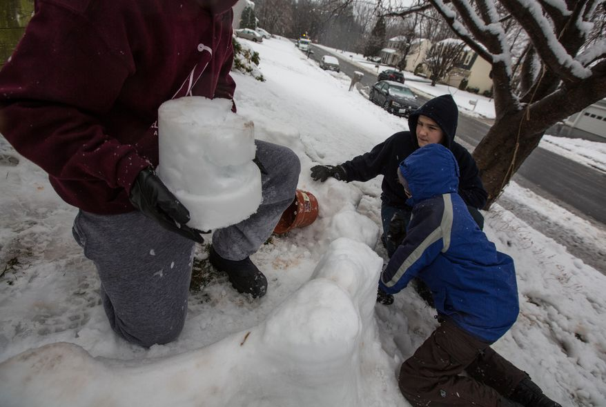 Mason Moy (left), 14, Sam Gustason (center), 13, and Calvin Crist, 13, build a snow fort in a front yard during a snow day in Fairfax, Va., on March 6, 2013. (Andrew S. Geraci/The Washington Times)