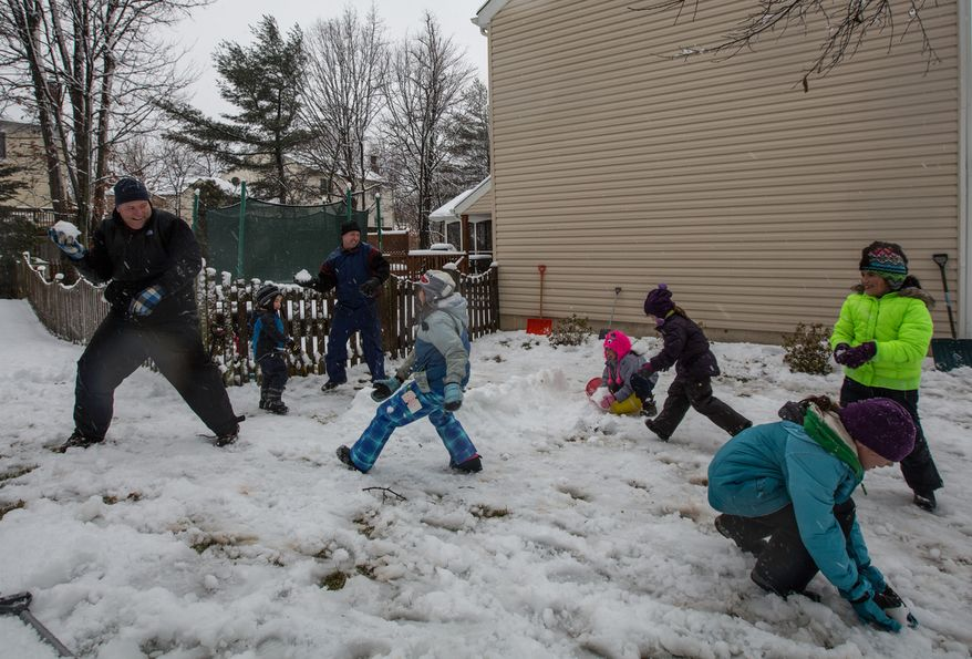 The Sweeney and Powers families engage in a snowball fight in Fairfax, Va., on March 6, 2013. (Andrew S. Geraci/The Washington Times)