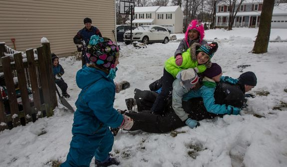 Members of the Sweeney and Powers families pile on top of Patrick Sweeney during a snowball fight in Fairfax, Va., on March 6, 2013. (Andrew S. Geraci/The Washington Times)