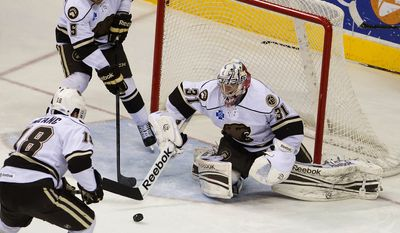 Hershey Bears goalie Philipp Grubauer (31) makes a save as Garrett Stafford (5) and Peter LeBlanc (18) help defend the net against the Syracuse Crunch during the second period of their AHL hockey game, Sunday, March 3, 2013, in Hershey, Pa. The Bears won 5-3. (AP Photo/Lebanon Daily News, Glen Gray)