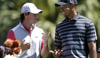 Tiger Woods, right, talks with Rory McIlroy, of Northern Ireland, as they wait to tee off at the 13th tee during the first round play at the Cadillac Golf Championship in Doral, Fla., Thursday March 7, 2013. (AP Photo/Wilfredo Lee)