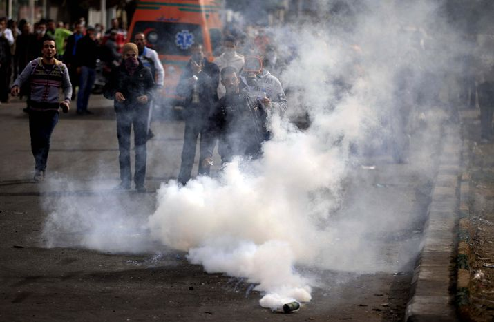 Egyptian protesters react from a tear gas canister fired by riot police, not pictured, during clashes near a state security building in Port Said, Egypt, Thursday, March 7, 2013. Clashes between protesters and police continued into a fifth day on Thursday in the restive Egyptian city of Port Said. (AP Photo/Khalil Hamra)
