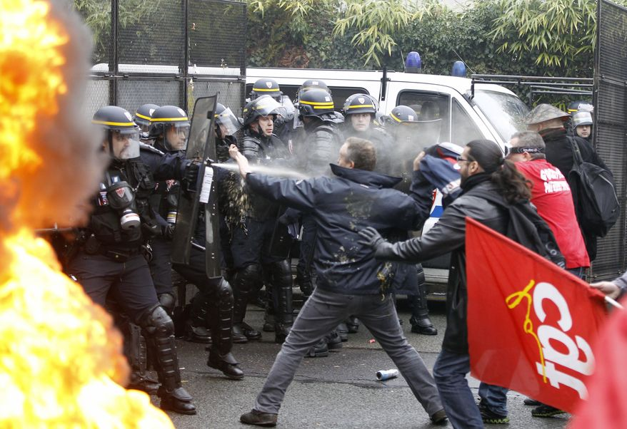 Goodyear employees scuffle with riot policemen during a demonstration against layoffs, in front of Goodyear headquarters in Rueil Malmaison, west of Paris, Thursday March 7, 2013. (AP Photo/Remy de la Mauviniere)
