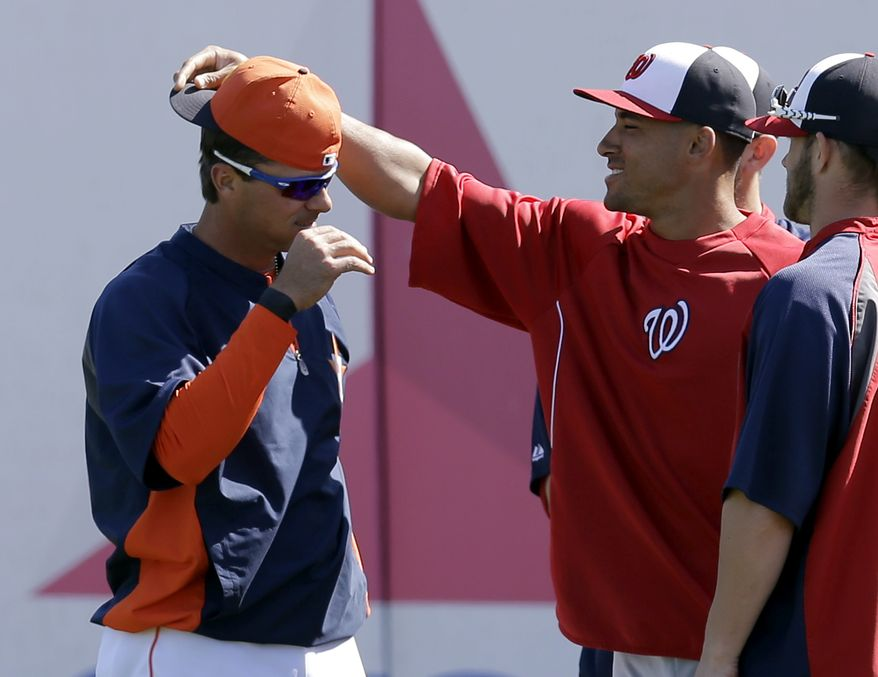 Washington Nationals' Ian Desmond, right, turns Houston Astros' Rick Ankiel's hat backwards during batting practice before an exhibition spring training baseball game Thursday, March 7, 2013, in Kissimmee, Fla. (AP Photo/David J. Phillip)