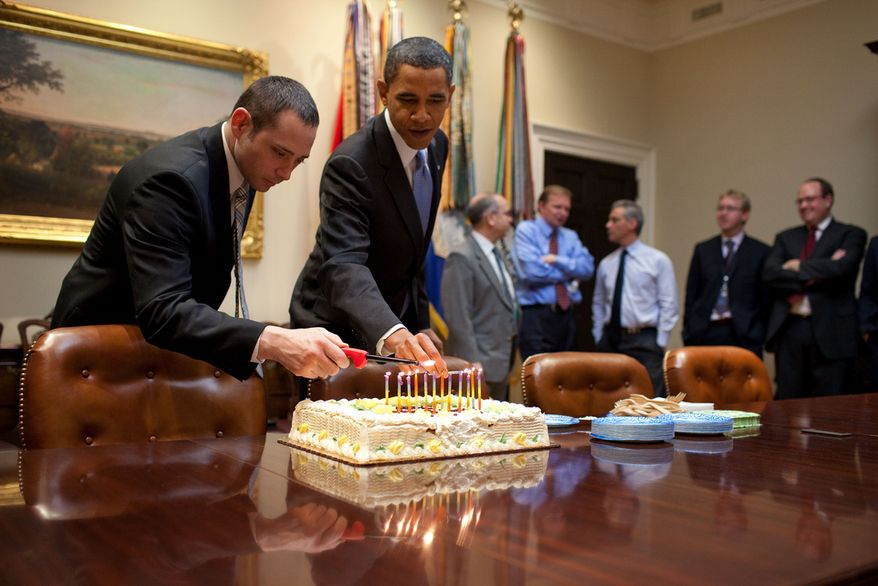 President Barack Obama and Oval Office Valet Raymond Rogers light candles on a birthday cake for NSC Chief of Staff Denis McDonough in the Roosevelt Room of the White House, Dec. 2, 2009.  (Official White House Photo by Pete Souza)