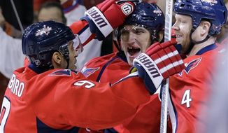 Washington Capitals center Mike Ribeiro (9), left wing Alex Ovechkin (8), from Russia, and defenseman John Erskine (4) celebrate Erskine's goal in the first period of an NHL hockey game against the Florida Panthers on Thursday, March 7, 2013 in Washington. (AP Photo/Alex Brandon)