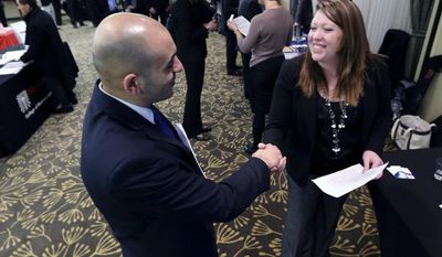 Sayed Mouawad (left) of Providence, R.I., shakes hands with Jillian Wallace of Matix Inc. during a job fair in Boston on Monday, Feb. 25, 2013. (AP Photo/Michael Dwyer)