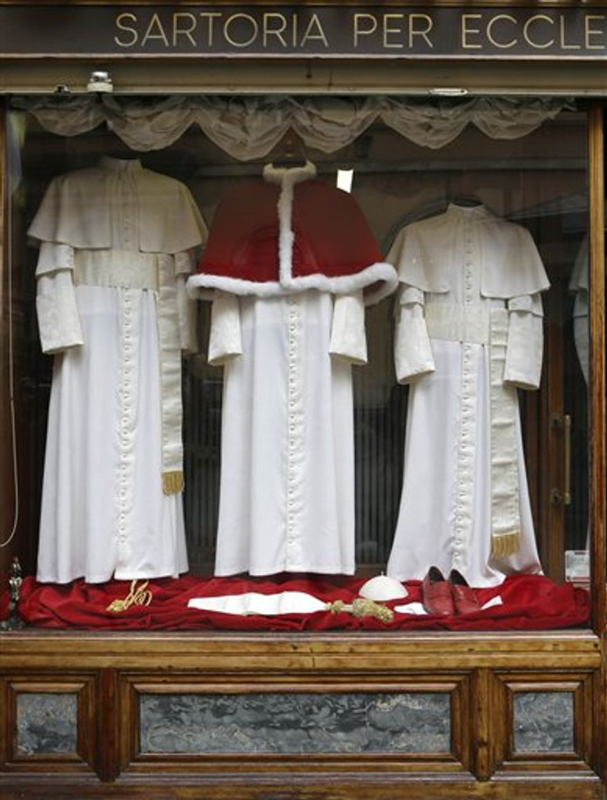 Three sets of papal outfits - small, medium and large sizes - are displayed in the window of the tailoring shop Gammarelli, in Rome. The Gammarelli family have been ecclesiastical tailors by papal appointment for over 200 years. (AP Photo/Andrew Medichini, Files)