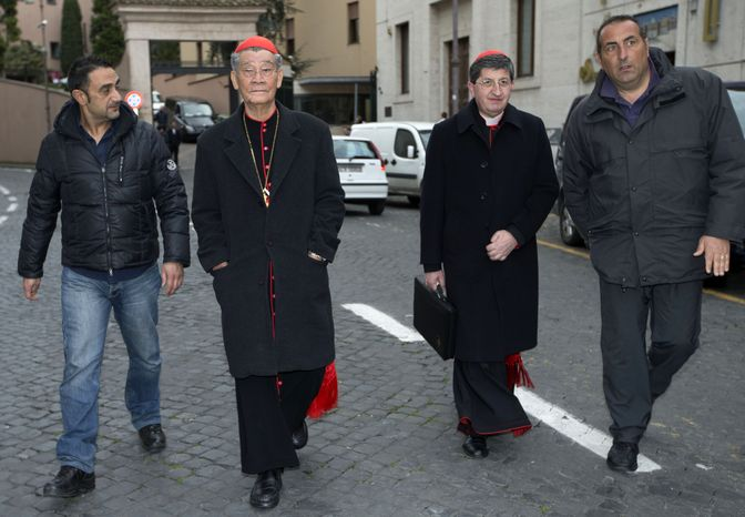 Cardinals Jean-Baptiste Pham Minh Man (second from left) of Vietnam and Cardinal Giuseppe Betori (second from right) of Italy are escorted to a meeting of fellow prelates at the Vatican on Thursday, March 7, 2013. Cardinal Man was the last of the 115 voting-age cardinals to arrive in Rome for the pre-conclave meetings. (AP Photo/Andrew Medichini)
