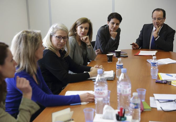 """French President Francois Hollande, right, his companion Valerie Trierweiler, third right, and Minister of Women's Rights Najat Vallaud-Belkacem, second right, attend a meeting with women at """"Force Femmes,"""" an association that helps unemployed women over 45 years old in Paris, Friday March 8, 2013. Hollande is proposing legislation to get more dads on long-term paternity leave and moms back to work faster. (AP Photo/Philippe Wojazer/Pool)"""