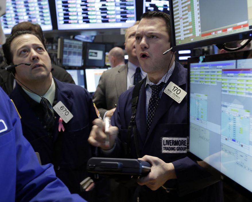 Tader Michael Zicchinolfi (right) works on the floor of the New York Stock Exchange on March 8, 2013. (Associated Press)