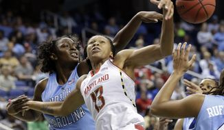 Maryland's Alicia DeVaughn, right, has her shot blocked by North Carolina's Waltiea Rolle, left, during the second half of an NCAA college basketball game at the Atlantic Coast Conference tournament in Greensboro, N.C., Saturday, March 9, 2013. North Carolina won 72-65. (AP Photo/Chuck Burton)