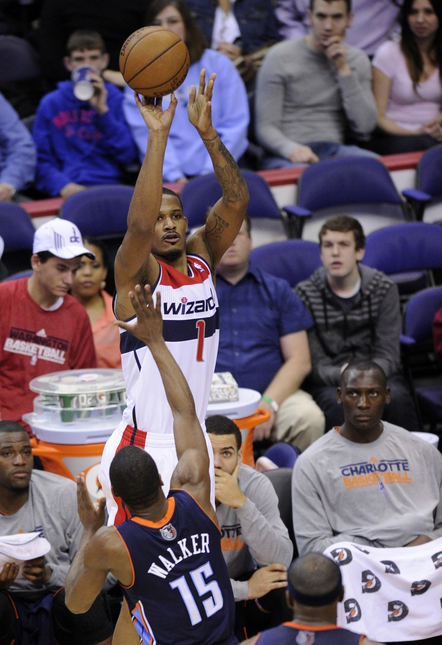 Washington Wizards forward Trevor Ariza (1) takes a shot over Charlotte Bobcats guard Kemba Walker (15) during the second half of an NBA basketball game, Saturday, March 9, 2013, in Washington. The Wizards won 104-87. (AP Photo/Nick Wass)