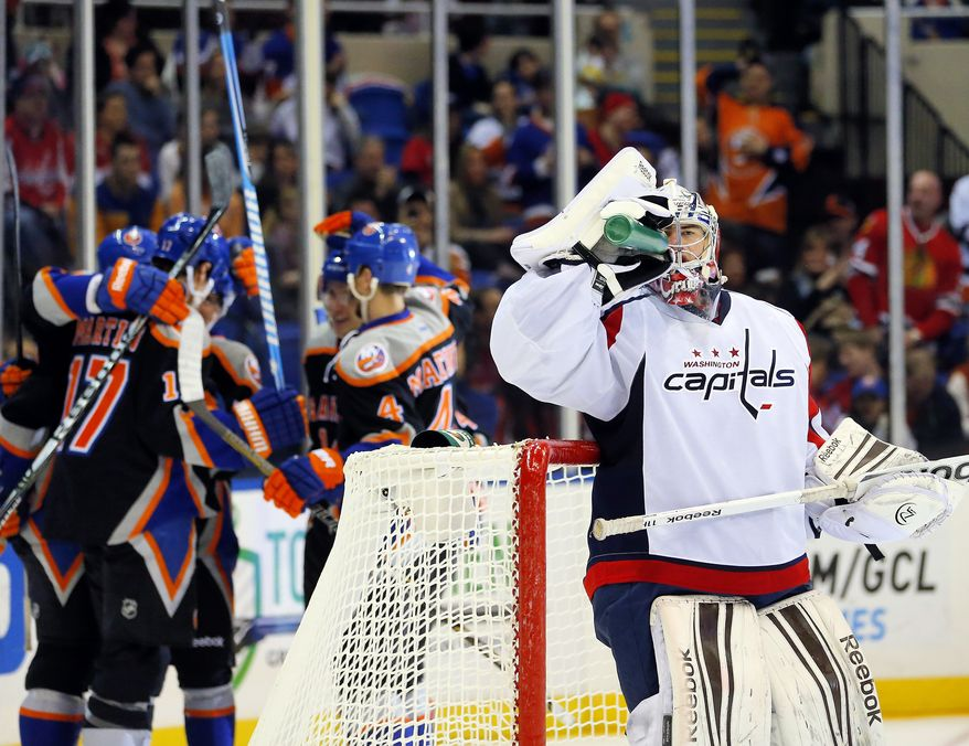 Washington Capitals goalie Philipp Grubauer (31) takes a drink as the New York Islanders celebrate a goal by Casey Cizikas during the second period of an NHL hockey game at the Nassau Coliseum in Uniondale, N.Y., Saturday, March 9, 2013. (AP Photo/Paul J. Bereswill)