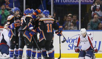 The New York Islanders congratulate teammate John Tavares (91) after scoring his first goal of the third period which turned out to be the winning goal as Washington Capitals defenseman Karl Alzner (27) kneels dejectedly in an NHL hockey game at the Nassau Coliseum in Uniondale, N.Y., Saturday, March 9, 2013. The Islanders won 5-2.(AP Photo/Paul J. Bereswill)