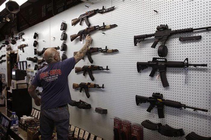 ** FILE ** Gun dealer Mel Bernstein takes down an AK-47 assault rifle from a sales rack at his own Dragonman's shooting range and gun store, east of Colorado Springs, Colo., Feb. 15. (AP Photo/Brennan Linsley)