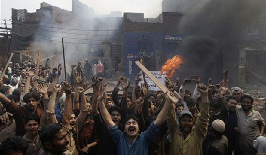 "FILE - An angry mob reacts after burning Christian houses in Lahore, Pakistan, Saturday, March 9, 2013. Hundreds of people in the eastern Pakistani city of Lahore attacked a Christian neighborhood Saturday and set fire to homes after hearing accusations that a Christian man had committed blasphemy against Islam's prophet Mohammed, said a police officer. Placard center reads, "" Blasphemer is liable to death."" (AP Photo/K.M. Chaudary)"
