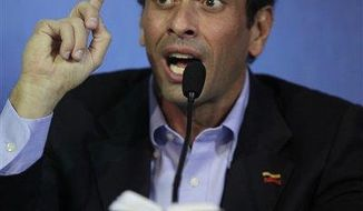 Opposition leader Henrique Capriles holds a miniature copy of Venezuela's Constitution as he speaks during a press conference in Caracas, Venezuela, Friday, March 8, 2013. Capriles called Vice President Nicolas Maduro a bold-faced liar and accuses him of using Hugo Chavez's funeral to campaign for the presidency.