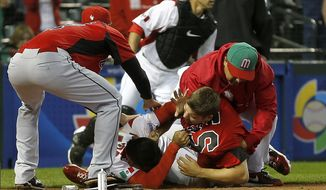 Canada's Jay Johnson, bottom right, and Mexico's Eduardo Arredondo fight during the ninth inning of a World Baseball Classic game as teammates try to break them up, Saturday, March 9, 2013, in Phoenix. (AP Photo/Matt York)