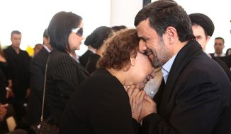 Iranian President Mahmoud Ahmadinejad comforts Elena Frias next to the flag-draped coffin of her son, the late Venezuelan President Hugo Chavez, during the funeral ceremony at the military academy in Caracas, Venezuela, on Friday, March 8, 2013. (AP Photo/Miraflores Press Office)