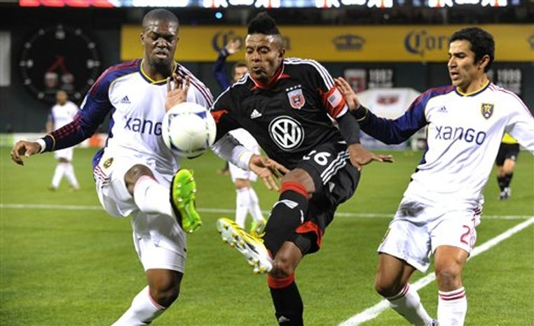DC United forward Lionard Pajoy, center, splits the defense of Real Salt Lake's Kwame Watson-Siriboe, left, and Tony Beltran (2) during the first half of an MLS soccer game on Saturday, March 9, 2013, in Washington. DC United defeated Real Salt Lake 1-0. (AP Photo/Richard Lipski)