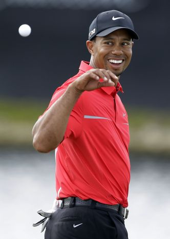 Tiger Woods looks back to catch a ball after his caddie cleaned it on the eighth green during the final round of the Cadillac Championship golf tournament on Sunday, March 10, 2013, in Doral, Fla. Woods won the championship. (AP Photo/Wilfredo Lee)