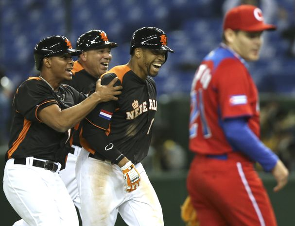 Netherlands' center fielder Kalian Sams, third from left, celebrates with teammate Xander Bogaerts, left, and coach Wirn Martinus after hitting a walk-off sacrifice fly off Cuba's pitcher Diosdany Castillo, right, in the ninth inning to beat Cuba 7-6 in their World Baseball Classic second round game at Tokyo Dome in Tokyo, Monday, March 11, 2013. (AP Photo/Toru Takahashi)