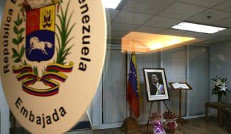 **FILE** A room with a portrait of the late Venezuelan President Hugo Chavez is prepared for supporters and members of the diplomatic corps to pay tribute and sign the book of condolences at the Venezuelan Embassy in the financial district of Makati city east of Manila, Philippines, on March 7, 2013. Chavez died Wednesday after a long bout with cancer. He was 58. (Associated Press)