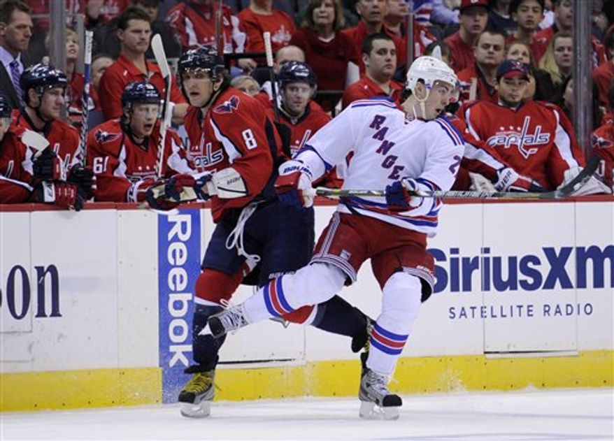 Washington Capitals left wing Alex Ovechkin (8), of Russia, becomes entangled with New York Rangers defenseman Ryan McDonagh, right, during the first period of an NHL hockey game on Sunday, March 10, 2013, in Washington. The Rangers won 4-1. (AP Photo/Nick Wass)
