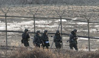 South Korean Army soldiers patrol along a barbed-wire fence near the border village of Panmunjom in Paju, South Korea, on March 11, 2013. North and South Korea staged dueling war games as threatening rhetoric from the rivals rose to the highest level since North Korea rained artillery shells on a South Korean island in 2010. (Associated Press)